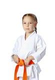 Mycket allvarlig liten flicka i en kimono med det orange bältet Fotografering för Bildbyråer