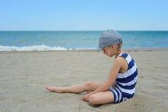 Mycket allvarligt gulligt liten flickasammanträde på stranden Royaltyfri Fotografi