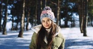 Mycket attraktiv asiatisk dam framme av le för kamera som är stort, och mening lyckligt i mitt av den snöig skogen henne arkivfilmer