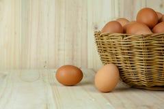 Mycket av ägg sätt i en vide- korg i träbakgrund royaltyfria bilder