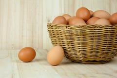 Mycket av ägg sätt i en vide- korg i träbakgrund royaltyfri bild