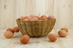 Mycket av ägg sätt i en vide- korg i träbakgrund arkivfoton