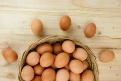 Mycket av ägg sätt i en vide- korg i träbakgrund fotografering för bildbyråer