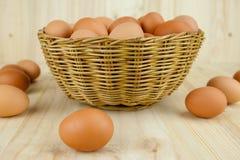 Mycket av ägg sätt i en vide- korg i träbakgrund arkivbilder