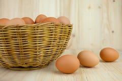Mycket av ägg sätt i en vide- korg i träbakgrund royaltyfri foto