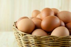 Mycket av ägg sätt i en vide- korg i träbakgrund arkivbild