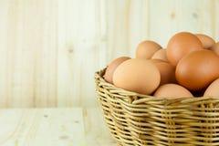 Mycket av ägg sätt i en vide- korg i träbakgrund royaltyfria foton