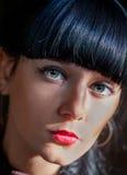 Mycket closeup av unga svarta haired kvinnor som ser kameran fotografering för bildbyråer