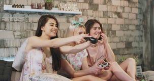 Mycket entusiastiska damer som spelar på en PlayStation lek på sängen i pyjamas, att le som är stort, och att tycka om tiden lager videofilmer