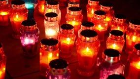 Mycket färgrika stearinljus som bränner på kyrkogården på natten Votive stearinljus glöder på grav All helgons dag Bönen tände st stock video