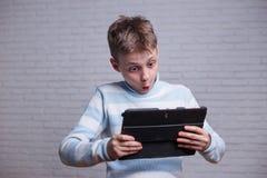 Mycket förvånad tonårs- pojke som ser minnestavlaPC i hans händer te royaltyfri foto