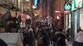 Mycket folk på de festliga gatorna av Stockholm Jul semestrar garneringar och belysningar i det smalt stock video
