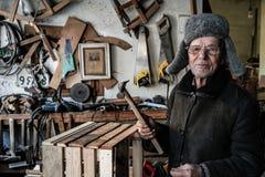 Mycket gamal manförlage i grått varmt kläder och glasögon med hammaren i händer arkivbild