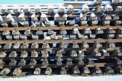 Mycket gamla stänger och längsgående stödbjälke staplas i ett järnväg lager i vinter Begreppet av att förnya en utsliten järnvägs royaltyfri fotografi