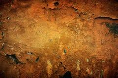 Mycket gammal guling-röd vägg med sprickor passande för bakgrund Arkivfoto