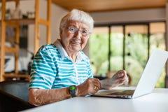 Mycket gammal hög kvinna som använder en dator arkivbild