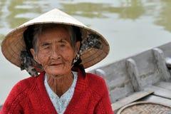 Mycket gammal infödd kvinna från Vietnam med den traditionella hatten Royaltyfria Bilder