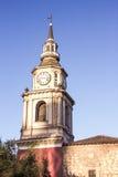 Mycket gammal kyrklig kyrktorn med klockan, korset och fäst liten byggnad för gammal tegelsten Arkivbilder
