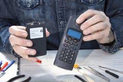 Mycket gammal mobiltelefon med ett stort batteri som framläggas av serviceanställd royaltyfri fotografi