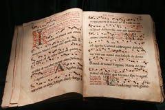 Mycket gammal öppen bibelbok som isoleras på svart Royaltyfri Bild