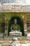 Mycket gammal stenskulptur av att sitta buddha som täckas med mossa och laver och dekoreras med pärlahalsbandet royaltyfria foton