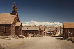 Mycket gammalt kulört tappningfoto med övergiven västra salongbyggnad i mitt av en öken Fotografering för Bildbyråer
