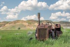 Mycket gammalt rostat traktorsammanträde i fält Fotografering för Bildbyråer