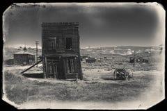 Mycket gammalt sepiatappningfoto med övergiven västra byggnad i mitt av en öken Royaltyfri Fotografi