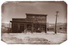Mycket gammalt sepiatappningfoto med övergiven västra salongbyggnad i mitt av en öken Fotografering för Bildbyråer