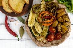 Mycket grönsaker som grillas på en maträtt (potatisar, tomater, morötter, lökar, zucchinin) Royaltyfri Fotografi