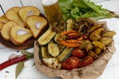 Mycket grönsaker som grillas på en maträtt (potatisar, tomater, morötter, lökar, zucchinin) Arkivfoto