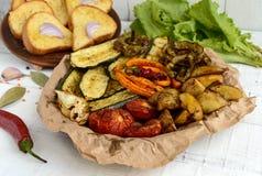 Mycket grönsaker som grillas på en maträtt (potatisar, tomater, morötter, lökar, zucchinin) Arkivbilder