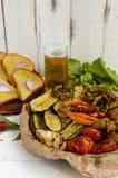 Mycket grönsaker som grillas på en maträtt (potatisar, tomater, morötter, lökar, zucchinin) Arkivbild