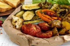 Mycket grönsaker som grillas på en maträtt (potatisar, tomater, morötter, lökar, zucchinin) Royaltyfri Foto