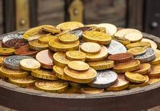 Mycket guld- mynt på en trätrumma arkivbilder