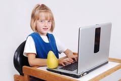 Mycket gullig blond flicka med bärbar dator på det isolerade skrivbordet Fotografering för Bildbyråer