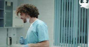 Mycket gullig karismatisk ung tandläkarecloseup framme av le för kamera som är stort och att ha ett bra lynne och att bära en blå arkivfilmer