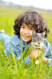 Mycket gullig liten flicka med katten på äng Arkivbild