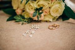 Mycket härlig bröllopbukett från vita rosor med guld- vigselringar och dyrbara örhängen Royaltyfri Foto