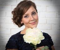 Mycket härlig mörk haired ung kvinna med den vita blomman Arkivfoton