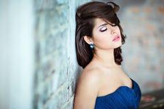 Mycket härlig sexig brunettflicka i en blå klänning som igen står royaltyfri fotografi