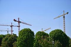 Mycket industriella kranar för höghus på bakgrund av den blåa himlen och de gröna träden arkivfoton