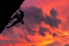 Mycket intressant ögonblick En ung mountainer har klarat av för att klättra till överkanten och för att uppnå hans mål fotografering för bildbyråer