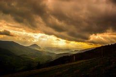 Mycket intressant solnedg?ng Sikt av v?rlandskap, solljus och m?rka moln ?ver royaltyfri bild
