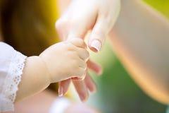 Mycket liten babys hand och hand av vuxna människan Royaltyfria Bilder