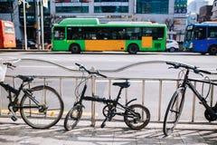 Mycket liten hopfällbar cykel på stadsgatan parkera på staketsideroad, den stads- platsen, cykeln och bussen royaltyfria bilder