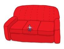 Mycket liten man som känner sig liten på soffan Royaltyfri Bild