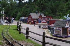 Mycket liten stad och miniatyrjärnväg, ungar som har gyckel royaltyfri foto