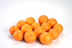 Mycket ljusa runda orange apelsiner ligger tillsammans på en vit bakgrund Fotografering för Bildbyråer