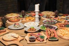 Mycket mat på trätabellen Georgisk kokkonst Top beskådar Lekmanna- lägenhet Khinkali och georgierdisk royaltyfri foto